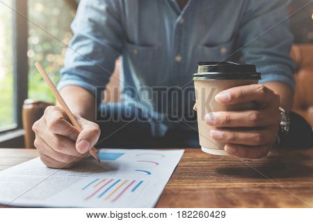 Close up Freelance or business man hands holding cup of coffee and writing on document with pencil. Graph financial diagram documents on wooden table.