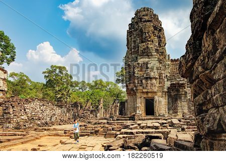 Siem Reap, Cambodia - February 2, 2016: Young tourist in front of the ruins of Prasat Bayon the central temple of Angkor Thom Complex. Visit to famous Cambodian landmark, World Heritage.