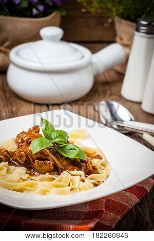 Tagliatelle with dark sauce. Italian cuisine. Selective focus.