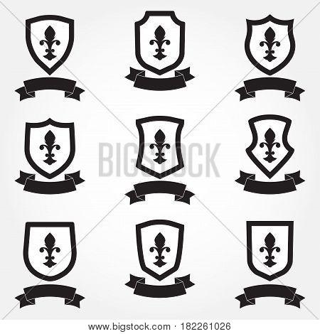Shields icon set. Different shield shapes with fleur-de-lis symbol and stylish ribbon. Heraldic royal design. Vector illustration.