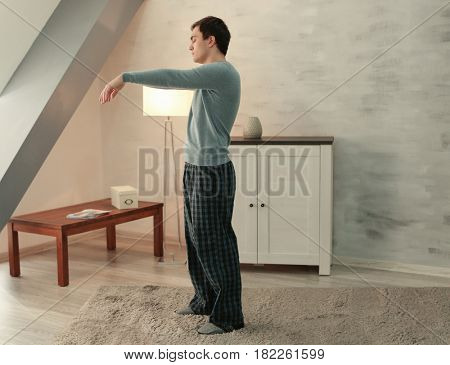 Young sleepy man sleep walking at home