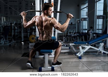 Fitness man with a naked torso trains on cable machine in the gym