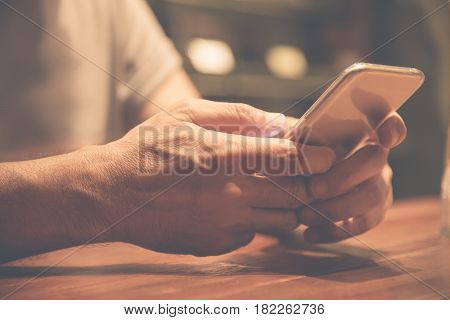 Close up on hands. Relaxed Asian Senior man using cell phone.