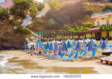 Bali Greece - April 30 2016: Sandy Evita and Karavostasi beach in sea bay of resort village Bali. Views of shore washed by waves and sun loungers with parasols where sunbathing tourists. Crete