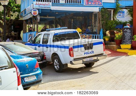Bali Greece - April 30 2016: Police white pickup Nissan Navara parked on Mithos beach promenade in sea bay of resort village Bali. Classic Greek stone architecture of resort tourists walk streets