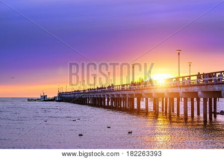 Ferroconcrete pillars of pedestrian seaside pier set in water on coast of Baltic sea. Passenger barge moored to bridge at sunset in resort Palanga Lithuania. Industrial & civil architectural design