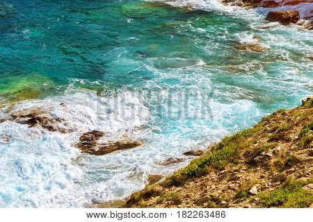 Waves break on rocky shore. Raging sea an elemental power in a storm. Clear day at sea coast. Tourist beach resort in village Bali Crete island Greece Beach Evita