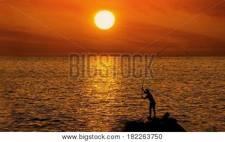 Silhouette of a fisherman on the background of round brilliant sunset in red colors and standing on a rock on the sea coast in the water.