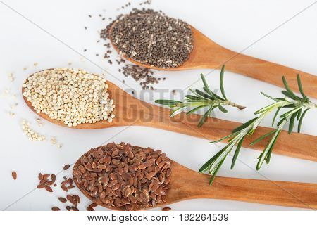 Healthy dried seed used as ingredients in cooking. Linseed, chia and quinoa in wooden spoons.