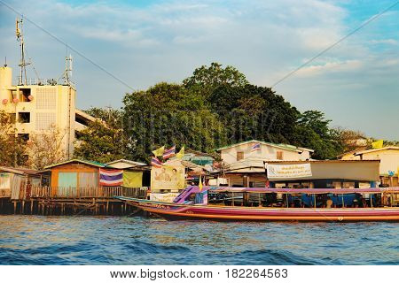 Bangkok, Thailand - December 8, 2015: People travelling by express boat in Chao Phraya river, Bangkok, Thailand. Old Thai traditional houses village riverfront.