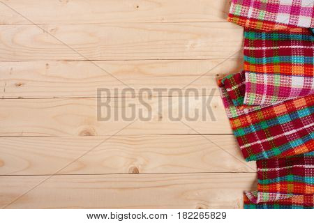 Red checkered tablecloth on a light wooden table with copy space for your text. Top view.
