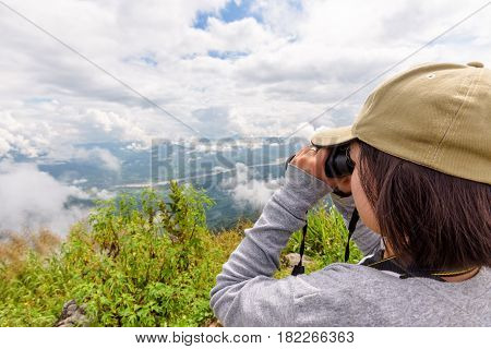 Woman tourist are using binoculars to see the beautiful natural landscape of the sky forest and mountain near the Mekong River at Doi Pha Tang view point in Chiang Rai Province Thailand