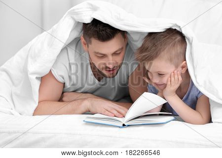 Dad and son reading interesting book while lying in bed at home