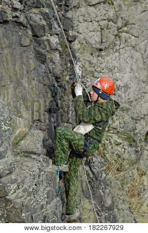 Beklenischevo, Russia - April 29, 2006: Rock climbing Woman rises on the rock by means of a rope and a zhumar up