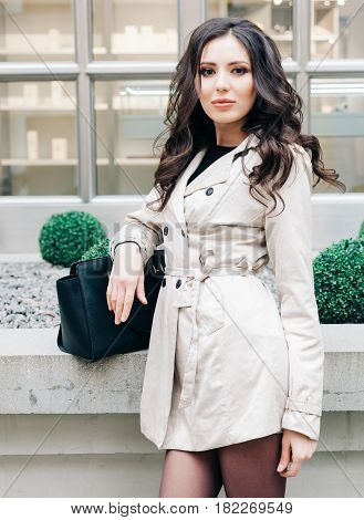 Fashionable brunette girl with long hair dressed in a raincoat, with big black hand bag posing near a boutique in Italy. Streetstyle. Fashion. Outdoor.