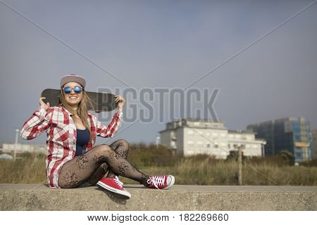 Smiling beautiful young woman holding a skateboard