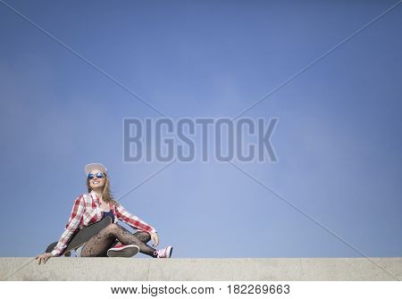Beautiful young skater girl posing with a skateboard against blue sky