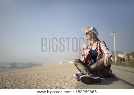 Smiling fashion young woman posing with a skateboard