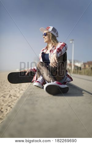 Happy smiling fashion young woman posing with a skateboard
