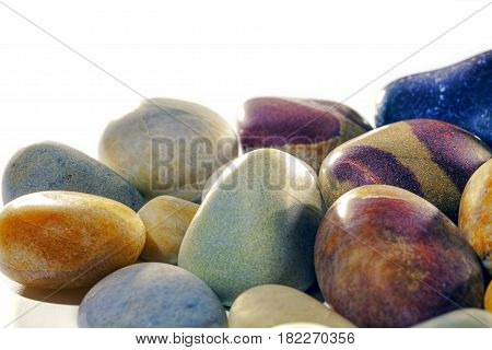 Colourful assortment of smooth tumbled beach pebbles studio shot against white background with copy space. The stones have been tumble polished to a satin shine.
