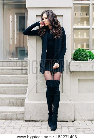 Attractive beautiful woman with fluffy brunette long hairs, posing on the gray wall, wearing black outfit and high black boots on heels, vacation style, autumn look, hairstyle, hairdresser. Fashion and Style.