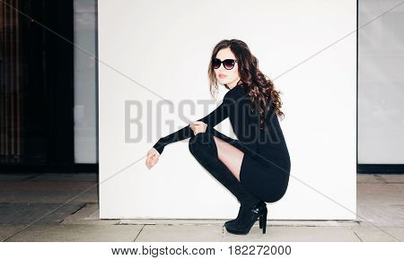 Night shot fashion portrait of brunette model in summer black clotches and sunglasses sitting near white wall. Style.