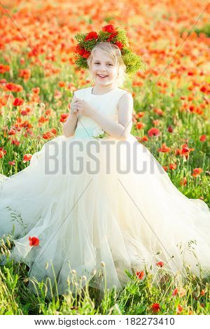 smiling young beautiful blonde with a wreath of flowers on her head, she in a white wedding dress in a field of poppies