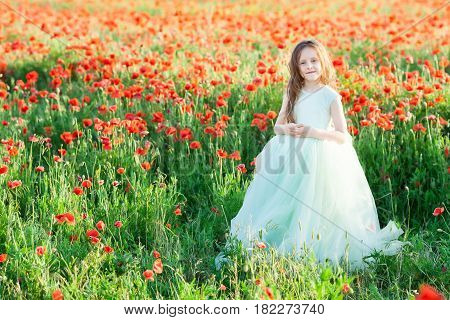little girl in the meadow of poppies, beautiful young lady in elegant dress, fingers crossed at chest level, in romantic mood