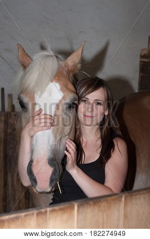 Young Woman Hugging Her Horse In Stable.