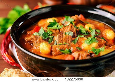 Goulash in ceramic bowl on wooden background. Traditional hungarian soup. Rustic style. Selective focus.
