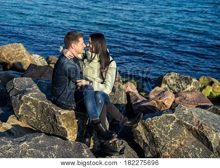 emotional couple sitting on the rocks on the beach with ocean on background. She is sitting on his lap and smiling. Moment before kiss.