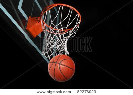 Basketball after going through hoop isolated over black background