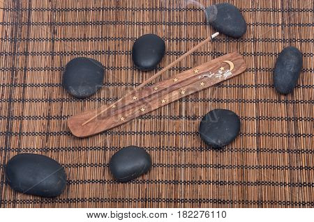 Hand carved burner, holder with sandalwood incense and polished black river pebbles on bamboo placemat