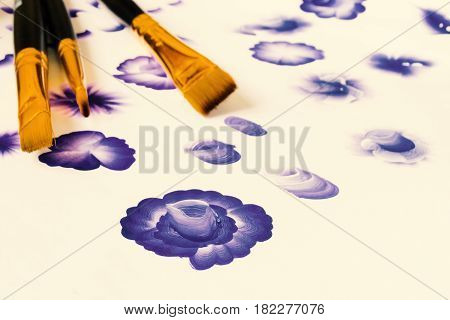 Three acrylic paint flat brushes. Basic one stroke painting painting strokes explained for beginners. Hand drawn folk blue flowers creative work place on black table