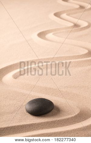 black hot stone for spa welness therapy. Rock on sand with raked line. Zen meditation garden background.