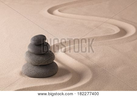 balancing black rocks in zen sand garden. Stone pile stacked in balance. Spa wellness or yoga background.