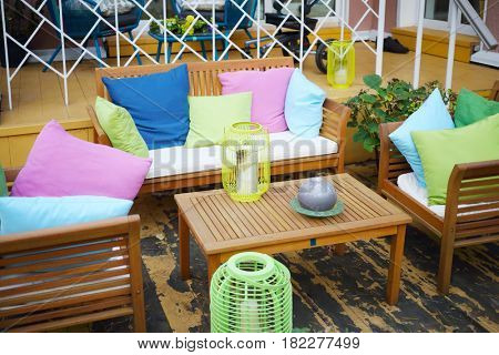 Empty cozy terrace with couch, table, candles, pillows for resting