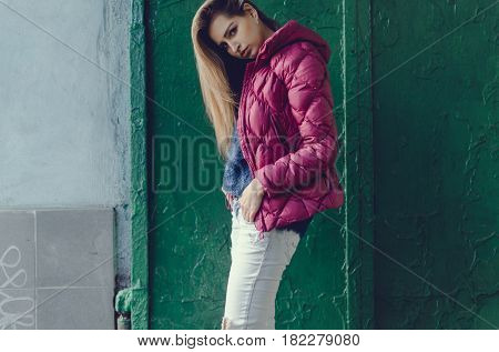 Woman on the street. Photo over green grunge wall. Wind in the autumn city.