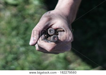 Bullets from AK Kalashnikov AK 47 in a clenched fist. The concept of war, the conflict in Syria