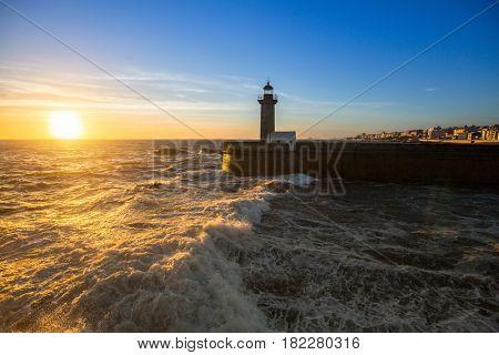 Beautiful sunset near the lighthouse on Atlantic coast of Porto, Portugal.