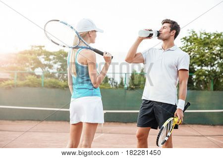 Young tennis couple. drinking water. on court