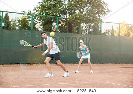 Handsome couple playing in tennis on court. side view. full length portrait