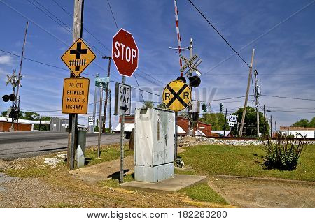 A series of road signs  on a busy street are in front of a city railroad crossing