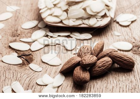 Sliced And Whole Raw Almonds On Wooden Surface