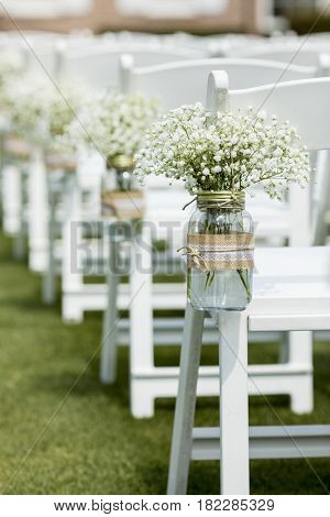 Mason jar with flowers hanging from chair at wedding