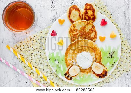 Easter funny bunny pancakes with fruit. Creative breakfast for kids of pancakes kiwi banana apple and juice on a white background top view