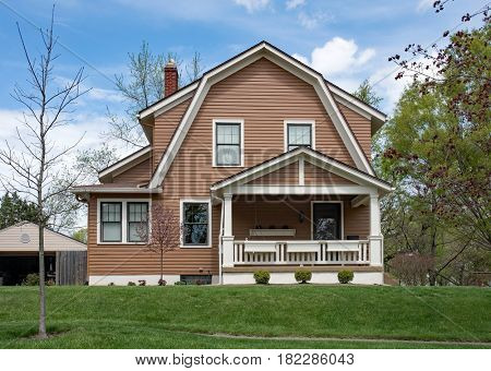 Brown House with Gambrel Roof in Springtime