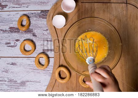 Egg Yolk And White In Glass Bowl And Wire Whisk Over Dark Weathered Wooden Table, Gingerbread