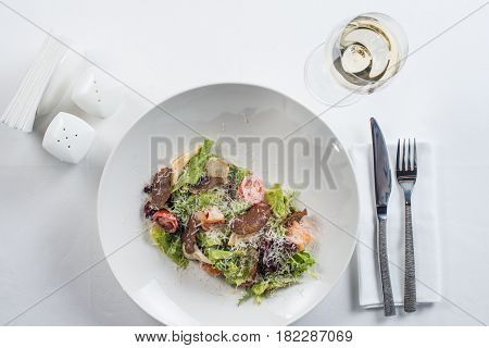 Seafood Caesar salad with shrimps, salad leaf, croutons, cherry tomatoes and Parmesan cheese white wine