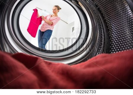 Young woman doing laundry - view from the washing machine